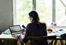 Bakre sikt av kvinnan som arbetar på datorbärbara datorn på trätabellen fotografering för bildbyråer