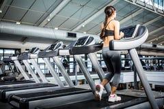 Bakre sikt av kvinnan som joggar i trampkvarn Arkivfoton