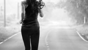 Bakre sikt av kvinnan som joggar på vägen Arkivbilder