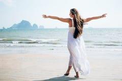 Bakre sikt av kvinnan som poserar med öppna armar royaltyfri fotografi