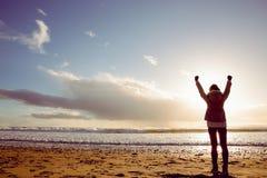 Bakre sikt av kvinnan som ser havet med händer upp royaltyfri foto