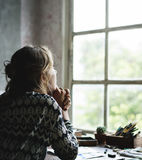 Bakre sikt av kvinnan som sitter fundersam utkik av fönstret Arkivfoton