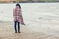 Bakre sikt av kvinnan som täckas med filten som ser havet på stranden Royaltyfri Bild