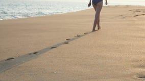 Bakre sikt av kvinnlig fot som går på guld- sand på stranden med havvågor på bakgrund Ben av den unga kvinnan arkivfilmer