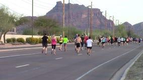 Bakre sikt av löpare som deltar i en maraton lager videofilmer