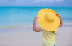 Bakre sikt av lilla flickan i en stor gul sugrörhatt Arkivfoto