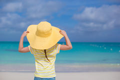 Bakre sikt av lilla flickan i en stor gul sugrörhatt på den vita sandstranden Royaltyfri Bild
