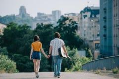 Bakre sikt av lyckliga gatamusiker som går och rymmer händer arkivbild