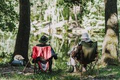 Bakre sikt av män som tycker om som fiskar på flodbanken fotografering för bildbyråer