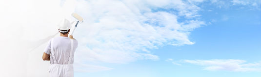 Bakre sikt av målaremannen som målar den blåa himlen på den tomma väggen fotografering för bildbyråer
