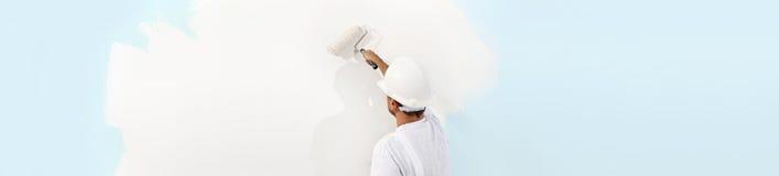 Bakre sikt av målaremannen som målar väggen, med målarfärgrullen, I royaltyfri fotografi