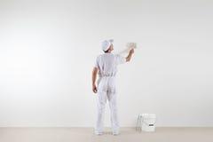 Bakre sikt av målaremannen som ser den tomma väggen, med målarfärgborsten arkivfoto