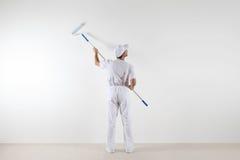 Bakre sikt av målaremannen som ser den tomma väggen, med målarfärgrolle arkivbilder
