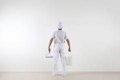 Bakre sikt av målaremannen som ser den tomma väggen, med målarfärgrolle royaltyfri bild