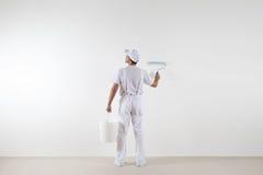 Bakre sikt av målaremannen som ser den tomma väggen, med målarfärgrolle Royaltyfri Foto