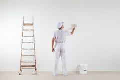 Bakre sikt av målaremannen som ser och målar den tomma väggen, med p royaltyfri fotografi