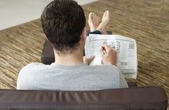 Bakre sikt av mannen som gör korsordpusslet i tidning Arkivbild