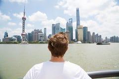 Bakre sikt av mannen som håller ögonen på Pudong horisont mot molnig himmel Royaltyfri Bild