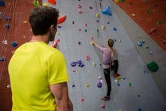 Bakre sikt av mannen som ser klättringväggen för kvinnlig idrottsman nen Arkivbild