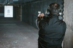 bakre sikt av mannen som siktar vapnet på målet royaltyfri foto