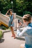 bakre sikt av mannen som tar bilden av den unga afrikansk amerikanflickvännen fotografering för bildbyråer