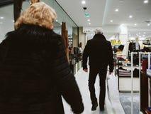 Bakre sikt av moderiktiga höga par som går i Printemps lyx de Royaltyfri Fotografi