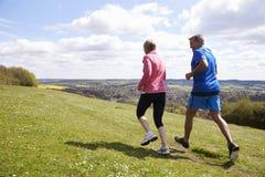 Bakre sikt av mogna par som joggar i bygd arkivbilder