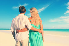 Bakre sikt av par med armar omkring på stranden royaltyfria bilder