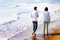Bakre sikt av par som går på stranden royaltyfria foton