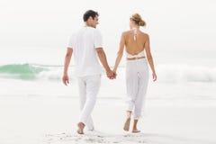 Bakre sikt av par som går på stranden arkivfoto