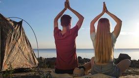 Bakre sikt av par som mediterar på kust nära tältet stock video