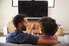 Bakre sikt av parsammanträde på Sofa Watching TV tillsammans arkivbilder