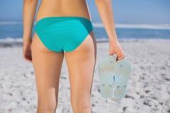 Bakre sikt av passformkvinnan i bikini på hållande flipmisslyckanden för strand Royaltyfri Fotografi
