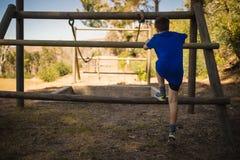 Bakre sikt av pojkar som klättrar utomhus- utrustning under hinderkurs arkivbild