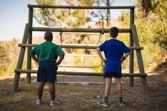 Bakre sikt av pojkar som ser utomhus- utrustning under hinderkurs arkivbilder
