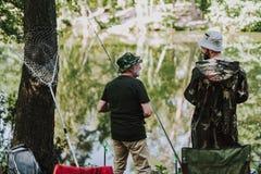 Bakre sikt av positiva sportfiskare som tycker om att fiska arkivbild