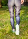Bakre sikt av rinnande sportskor för aktiv kvinna Arkivbild