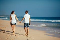 Bakre sikt av romantiska lyckliga par som går på stranden som rymmer händer på bakgrund för blå himmel och hav Man och kvinna in arkivfoto