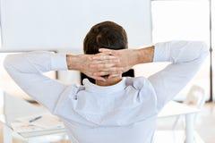 Bakre sikt av sammanträdeaffärsmannen med korsade händer på huvudet Arkivfoto