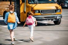 bakre sikt av skolflickor med ryggsäckar som kör till arkivbilder