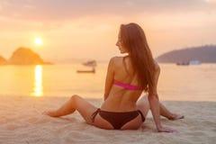 Bakre sikt av slankt kvinnligt modellsammanträde på den bärande bikinin för kust som ser bort under soluppgång med den reflektera arkivfoto