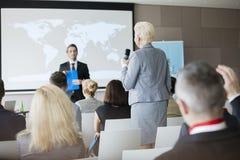 Bakre sikt av svarande frågor för affärskvinna under seminarium Arkivbild