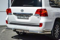 Bakre sikt av Toyota Land Cruiser 200 i vit f?rg, n?r att ha gjort ren f?r f?rs?ljning i en solig dag p? parkering arkivbild