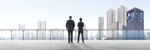 Bakre sikt av två asiatiska affärspersoner som står på modern terrass och ser sikt royaltyfri fotografi