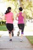 Bakre sikt av två kvinnliga löpare på den förorts- gatan Royaltyfria Bilder