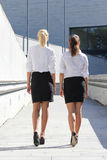 Bakre sikt av två unga attraktiva affärskvinnor som går på stre Royaltyfri Foto