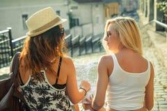 Bakre sikt av två unga kvinnor med stadsöversikten i sökande av dragningar Unga turist- flickavänner som reser på ferier Sommar v Arkivbilder