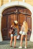Bakre sikt av två unga kvinnor med stadsöversikten i sökande av dragningar Unga turist- flickavänner som reser på ferier Sommar v Fotografering för Bildbyråer