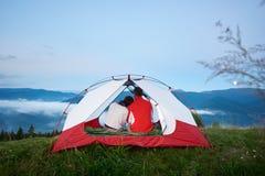 Bakre sikt av unga par som sitter i tältet som ser berg fotografering för bildbyråer