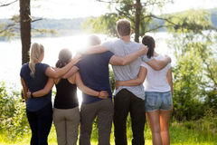 Bakre sikt av vänner som omkring står armar i skog Royaltyfria Bilder